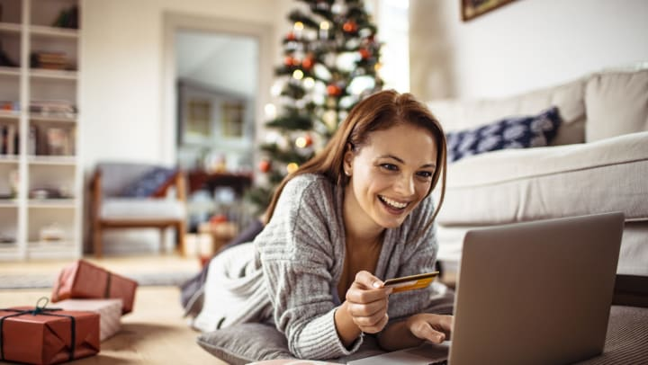 A young woman lying on the floor holds a credit card while she shops online online, with wrapped presents next to her and a decorated tree in the background