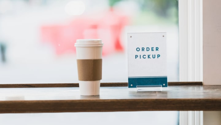 Takeout cup of coffee next to order pickup sign