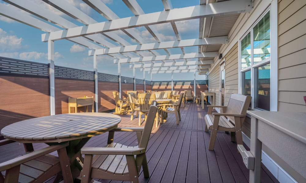 Deck with patio tables and pergola at The Sanctuary at St. Cloud in St. Cloud, Minnesota