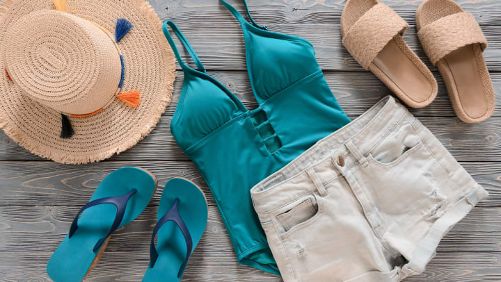 A big hat and bathing suit laid out with shorts and sandals on a wood background.