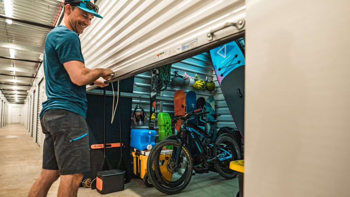 Man closing the door of a self storage unit full of outdoor gear