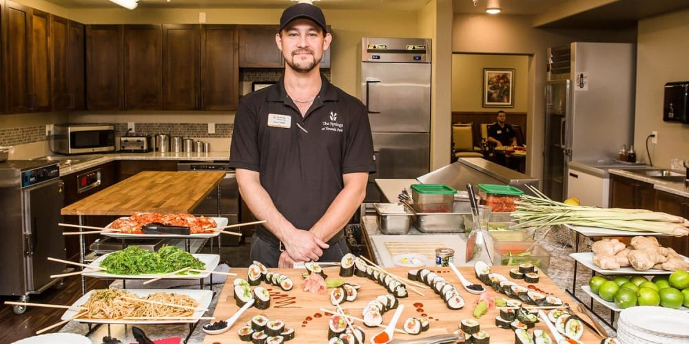 Chef in front of sushi buffet for residents of The Springs at Veranda Park in Medford, Oregon
