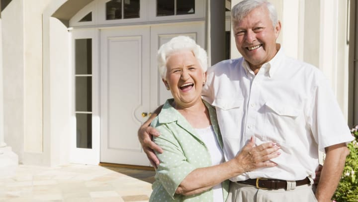 Elderly couple photographed in front of their new home.