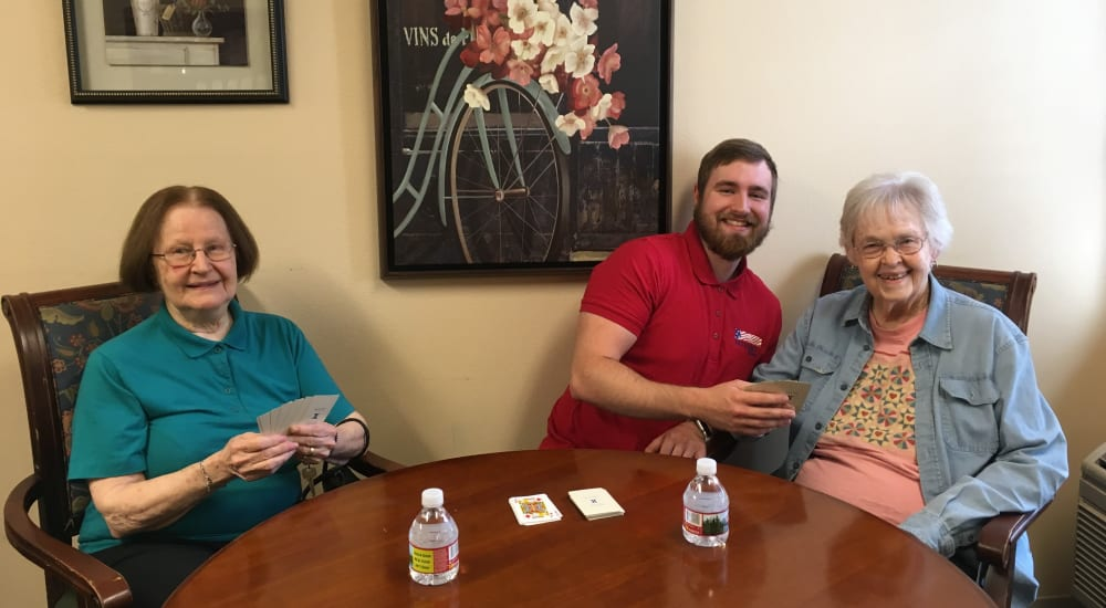 Memory care residents playing a game of cards at Patriots Glen in Bellevue, Washington.