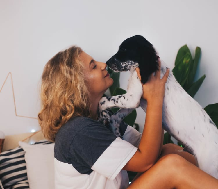 Resident giving her puppy a kiss in her new home at Haven Warner Center in Canoga Park, California