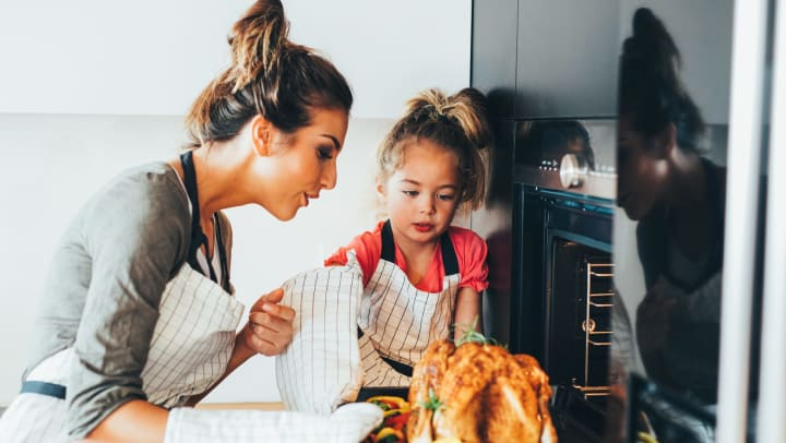 Mom and daughter pulling a delicious turkey out of the oven at Cape House