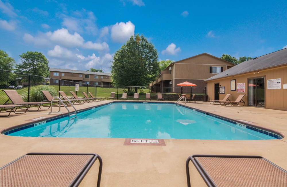 Swimming pool with tables and umbrellas at 1022 West Apartment Homes in Gaffney, South Carolina
