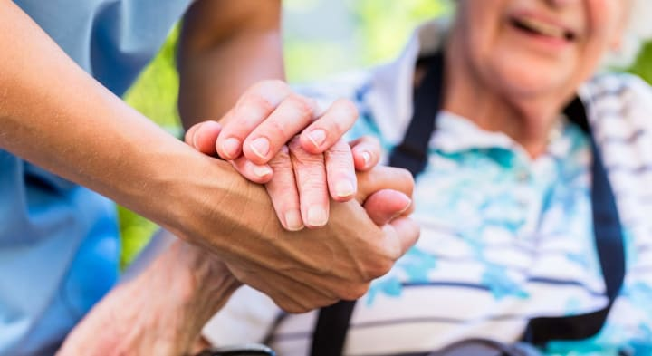 Caregiver and senior holding hands