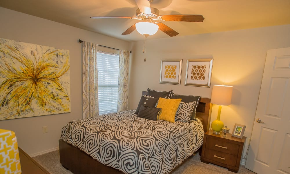 Cozy bedroom with a ceiling fan at Tuscana Bay Apartments in Corpus Christi, Texas