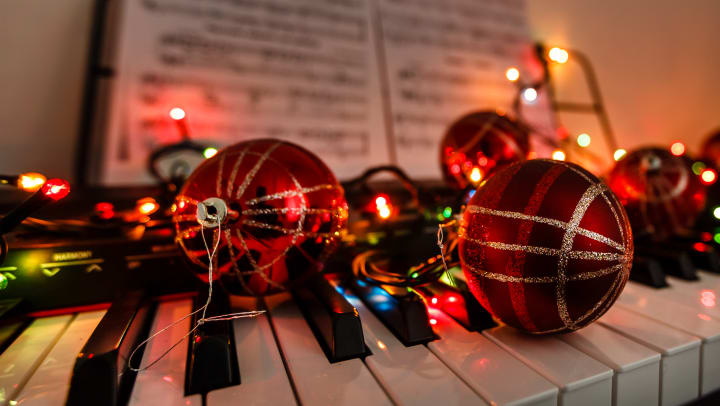 A piano keyboard decorated with holiday ornaments and lights.