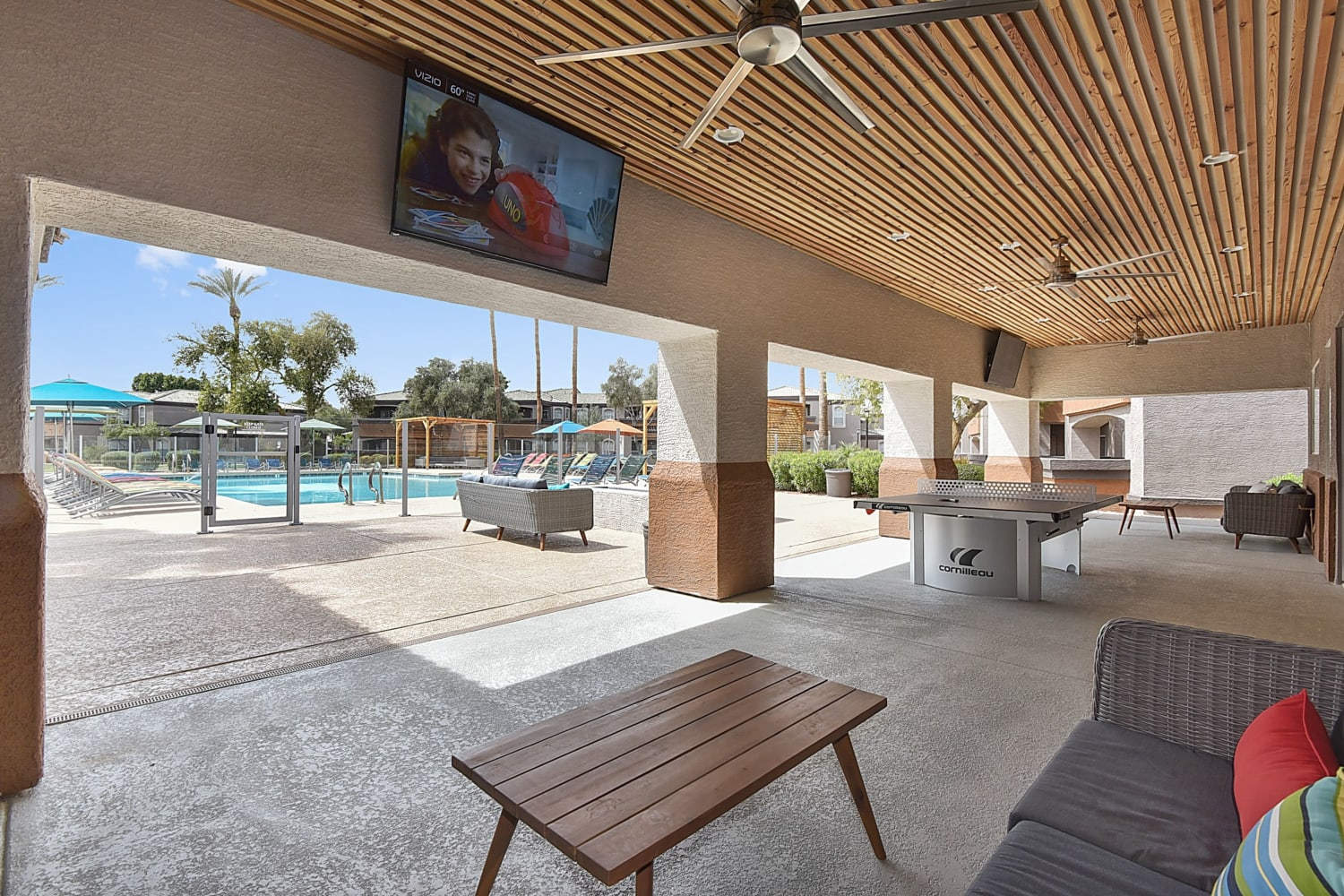 Covered patio seating with ping pong and a TV at Luxe @ Ocotillo in Chandler, Arizona