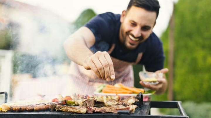 Man cooking on an outdoor grill at {{location_name}}.