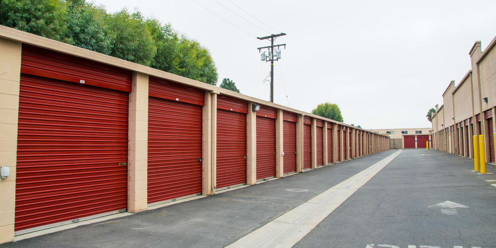 Drive-up storage units with red doors at StorQuest Self Storage in Long Beach, California