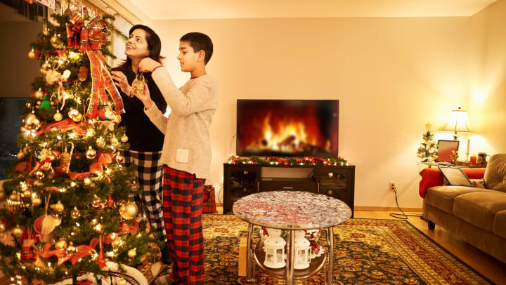 Mother and son decorating their Christmas tree with an electronic fire in the background