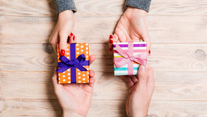 Top view of two people's hands exchanging gifts
