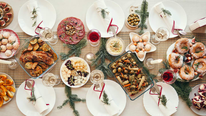 A festively decorated holiday table with a large spread of food is viewed from above.