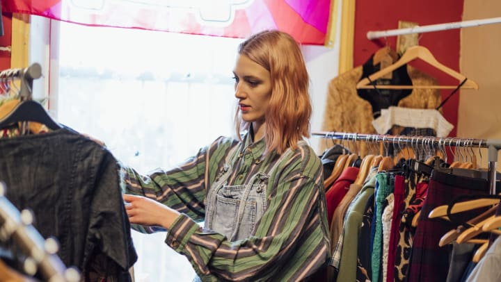 A woman wearing overalls and a loose long-sleeved shirt looking at a rack of clothing in a light-filled store
