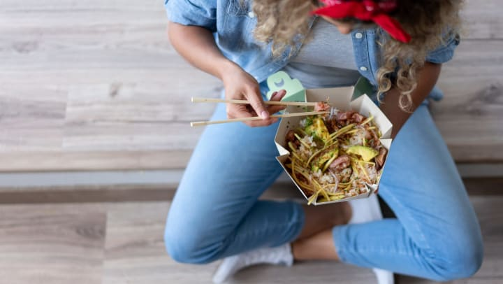 Woman eating out of a takeout container