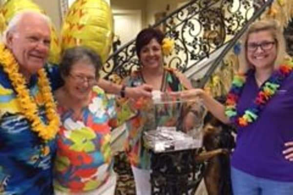 Team members of Discovery Senior Living having a great time during the Luau Cruise Craze at Champion Forest in Bonita Springs, Florida