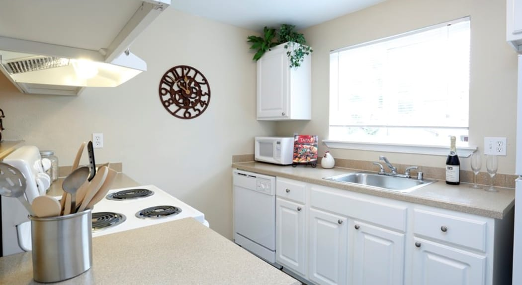 Spacious and bright kitchen in model home at Discovery Landing Apartment Homes in Burien, WA