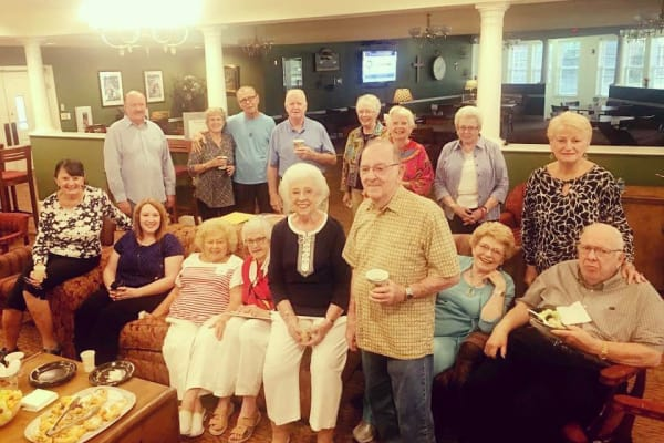 Residents lakeside enjoying a coffee chat at Discovery Senior Living in Bonita Springs, Florida