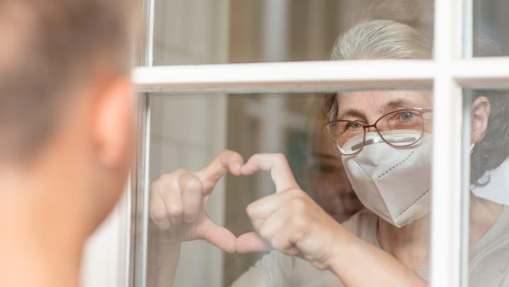 Elderly woman holding heart hands towards loved one outside of window