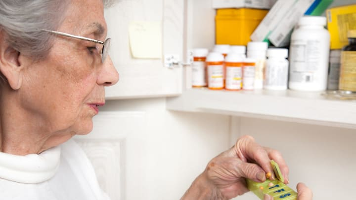 Senior woman standing in front of an open medicine cabinet placing pills into a daily pill container.