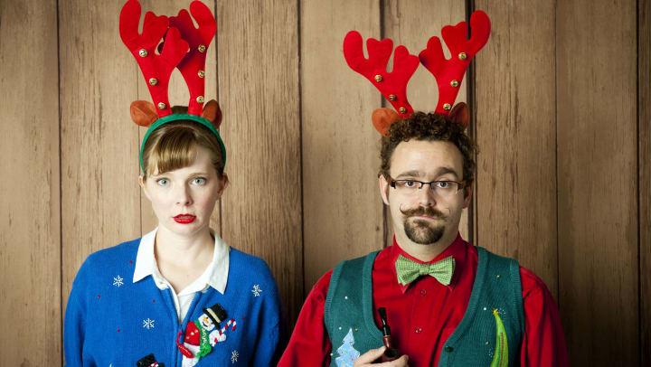Couple wearing ugly Christmas sweaters