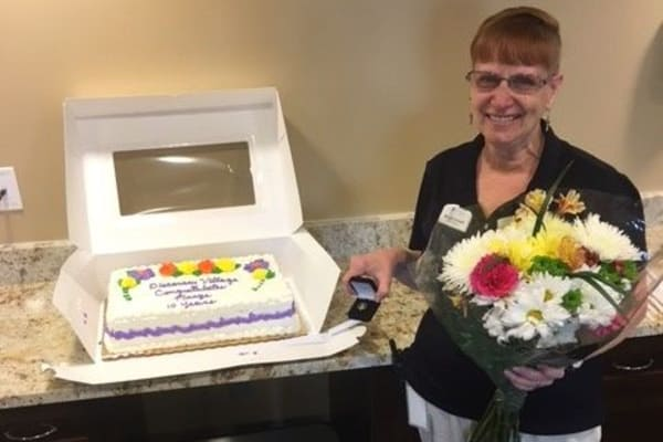 Employee holding flowers and celebrating 10 years as a team member at Discovery Senior Living in Bonita Springs, Florida