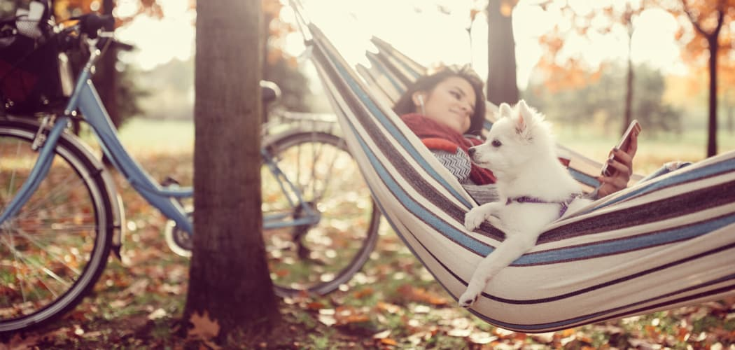 Resident and her dog relaxing in a hammock among the trees at Residences at Sonoma Woods in Newport News, VA