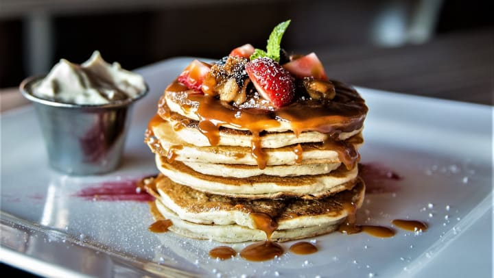 Beautiful stack of pancakes topped with fresh berries, nuts, and syrup at Olympus Northpoint in Albuquerque, New Mexico