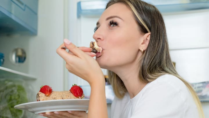 Resident taking a bite from a slice of ice cream cake in her apartment at Olympus Steelyard in Chandler, Arizona