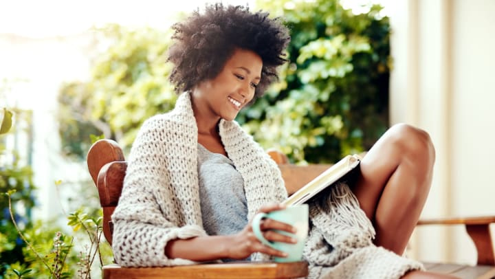 Woman happily sitting outdoors with coffee and a book at Olympus Property in fort Worth Texas