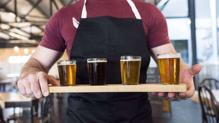 Server carrying a a flight of beers to a table at a restaurant near Olympus at Auburn Lakes