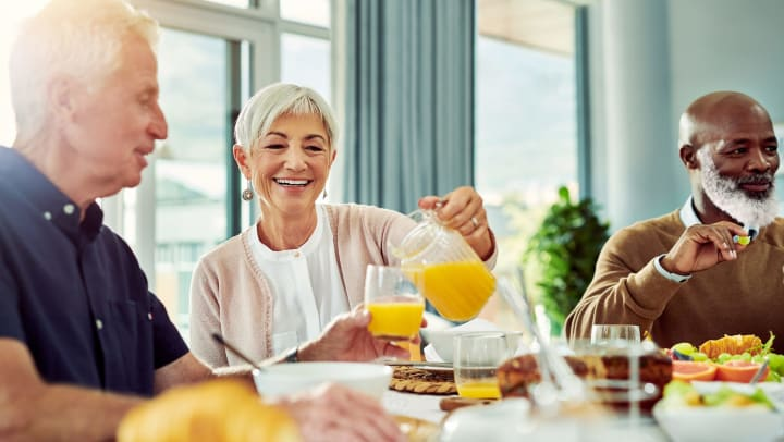 A smiling senior woman pours orange juice into a glass held by a senior man, as they eat breakfast at a table with another man.