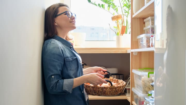 Resident pulling some items from her pantry for dinner in her apartment home at Olympus Katy Ranch in Katy, Texas