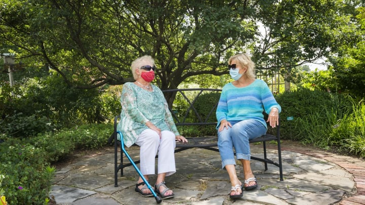 Two women socially distanced and wearing face masks sitting on an outdoor bench.