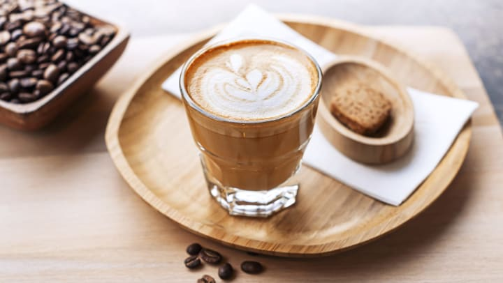 Coffee drink in a short glass sitting on a wooden plate, with a dish of coffee beans in the background