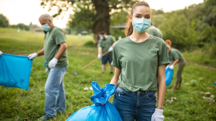 A woman in a mask and work gloves holds a large plastic bag of trash, while other volunteers in the background continue cleaning up trash from a natural area.