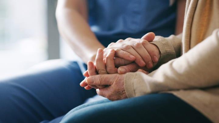 Senior holding hands with a caregiver