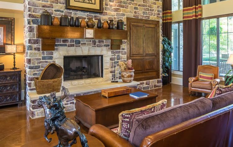 Rustic clubhouse with a large fireplace and plenty of seating for entertaining guest at Ranch ThreeOFive in Arlington, Texas