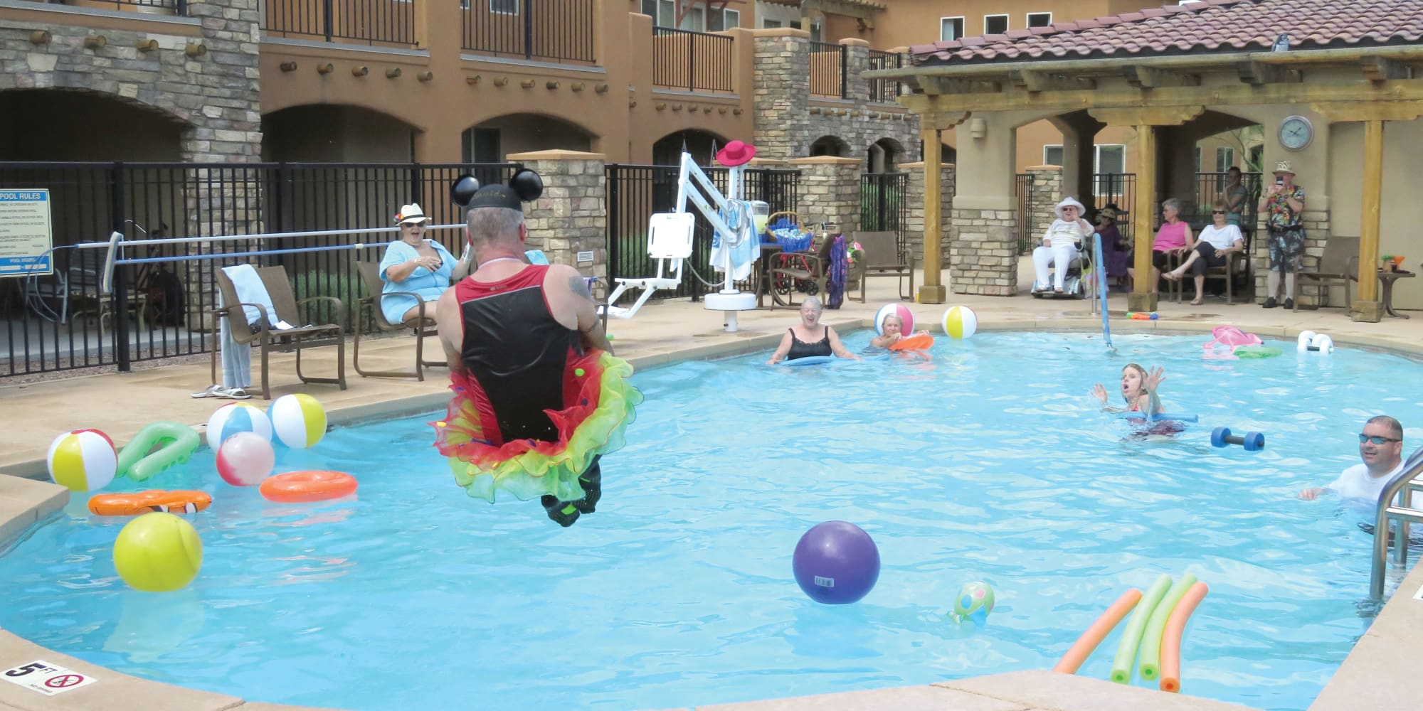 A resident dressed as mickey mouse jumping into the pool at Desert Springs Gracious Retirement Living in Oro Valley, Arizona