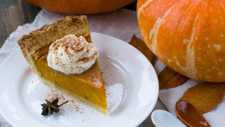 A slice of pumpkin pie with whipped cream is displayed in front of a pumpkin and to the left of two spoons.