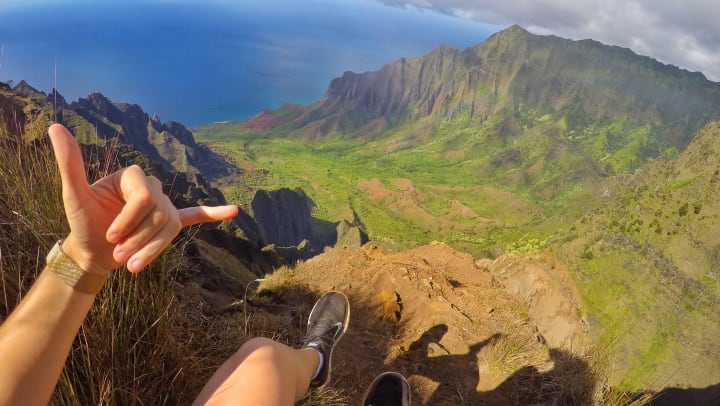 "Person gesturing the ""hang loose sign while sitting on top of a cliff overlooking the Ocean and rugged mountain peaks"