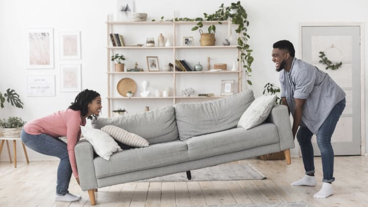 A woman and man lift opposite ends of a couch while moving.
