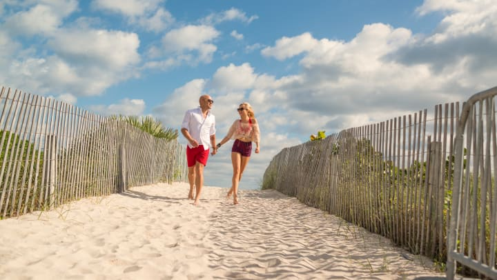 Man and woman holding hands while walking on a beach.