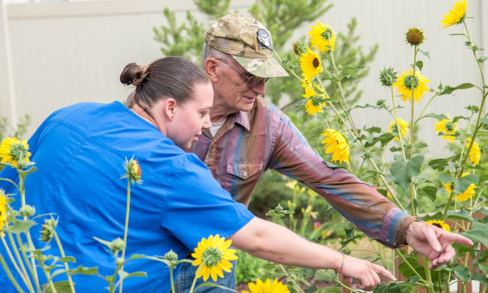 A resident and caretaker looking at sunflowers at Touchmark at Coffee Creek in Edmond, Oklahoma