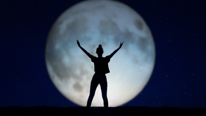 Woman doing yoga in front of a full moon