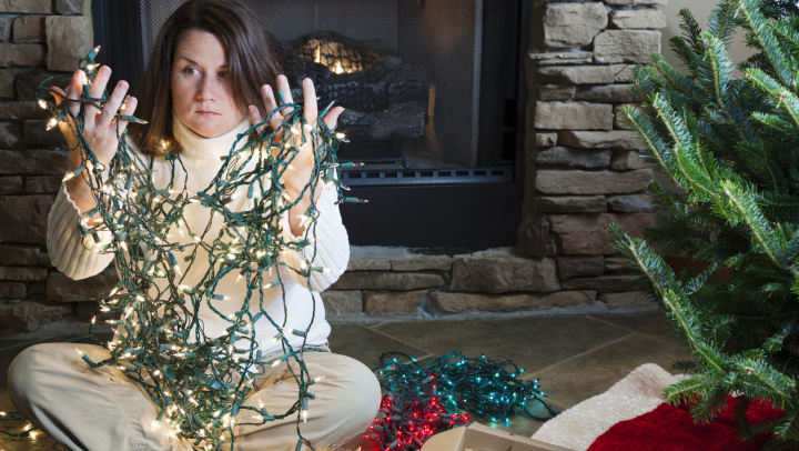 A young woman holds a tangle of string lights while sitting on the floor next to a holiday tree and boxes of ornaments.