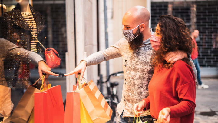 Man and woman with shopping bags and face masks looking in a store window